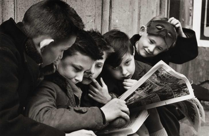 """<i>Thursday, reading the """"Compagnons de la section noire"""" on the pavement in the rue Rousselet in Paris</i>, photography by Janine Niépce (1956)"""